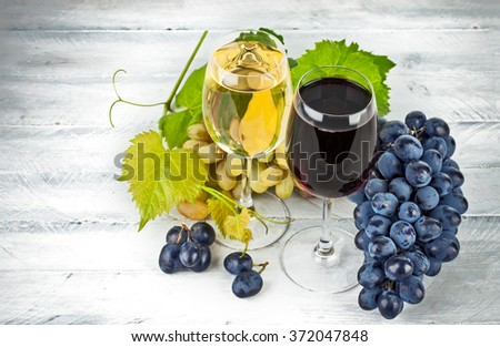 Red white wine in wineglass with grapes green willow wooden board - stock photo