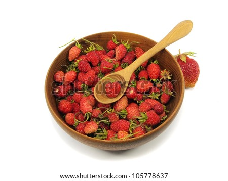 Red wild strawberry in wooden bowl on a white background