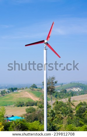 Red wind turbine, wind generator, wind power unit or wind energy converter working on hill - stock photo