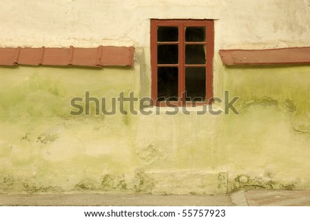 Red window on an ancient wall - stock photo