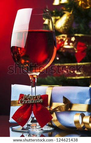 Red wine and Christmas decoration gifts tinsel - stock photo