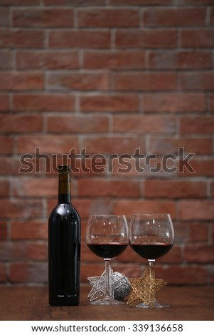 Red wine and Christmas ornaments on wooden table on wall brick background