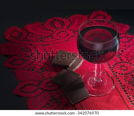 Red wine and dark chocolate on red lace. Chiaroscuro style. Healthy heart foods. - stock photo