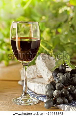 Red wine and grape on the wood surface, outdoor