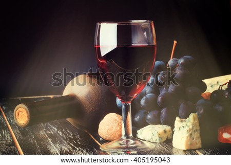 red wine and grapes on an old shabby wooden background bottle of dusty retro rustic style