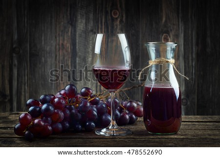 Red wine and grapes on vintage wooden board