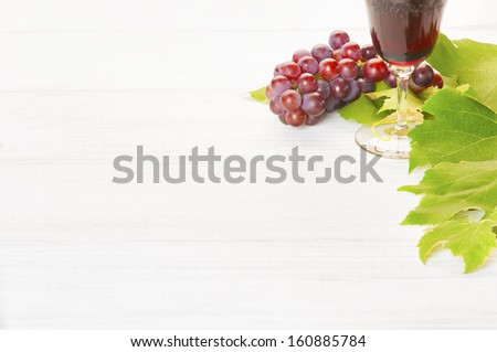 Red Wine and Grapes with Leaves on white wood background, a horizontal with room or space for your words, text or copy - stock photo
