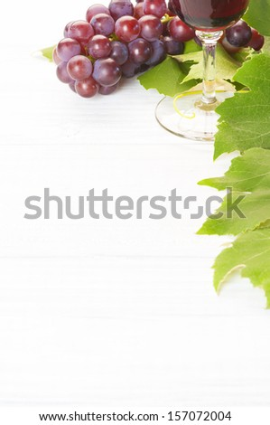 Red Wine and Grapes with Leaves on white wood background, a vertical with room or space for your words, text or copy - stock photo