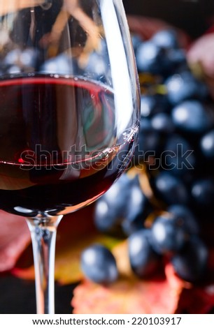 red wine and new crop of grapes for wine manufacture, focus on glass