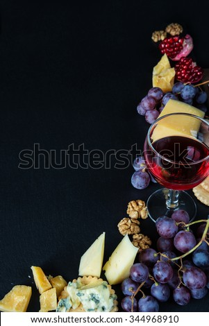 Red wine and snacks arranged in the form of a corner on a black background - stock photo