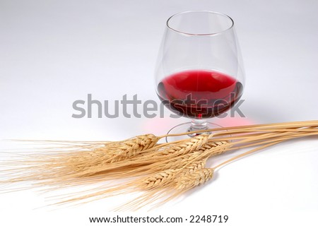 Red wine and wheat on a light background - stock photo