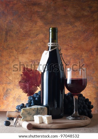 Red wine, assorted cheeses, and grapes in a still life setup. - stock photo