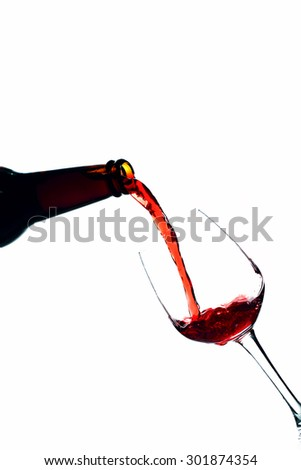 Red wine being in glass isolated on white background. Splashing stop motion.