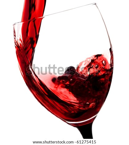 Red wine being poured in a wine glass - stock photo
