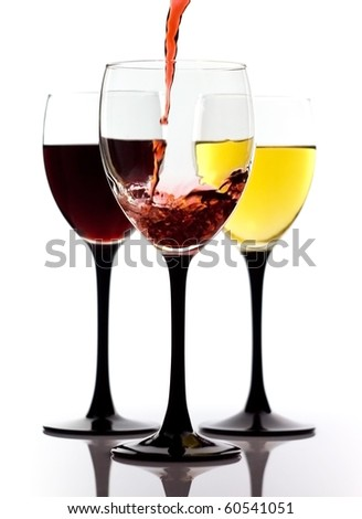 Red wine being poured in a wine glass and two glasses with white and red wine on a background - stock photo