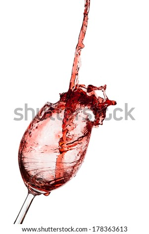 red wine being poured into a glass on a white background
