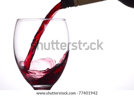 Red wine being poured into a glass, white background.