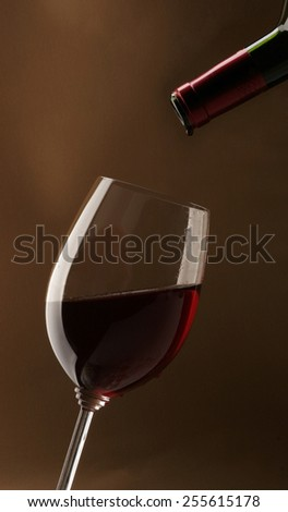 Red wine being poured into crystal glass - stock photo