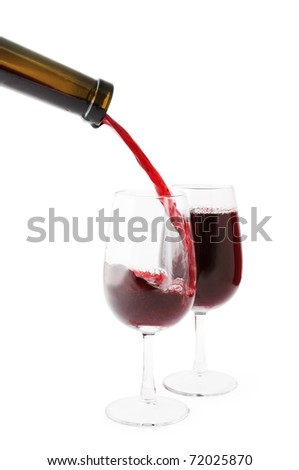 Red wine being poured into one of two glasses. Isolated on white, clipping path included.
