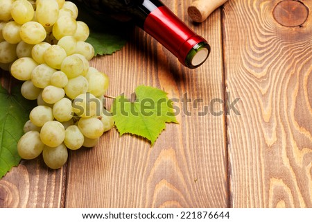 Red wine bottle and bunch of white grapes on wooden table background with copy space - stock photo