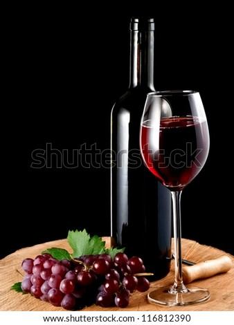 Red wine bottle and glass and grapes on a stump