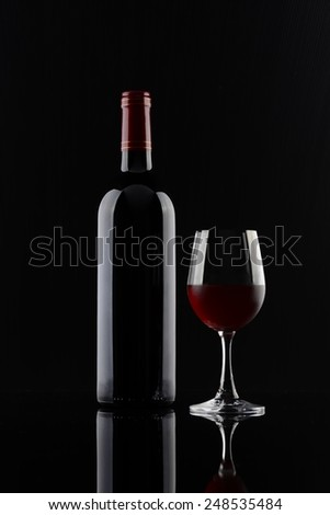 Red Wine bottle and glass on black background - stock photo