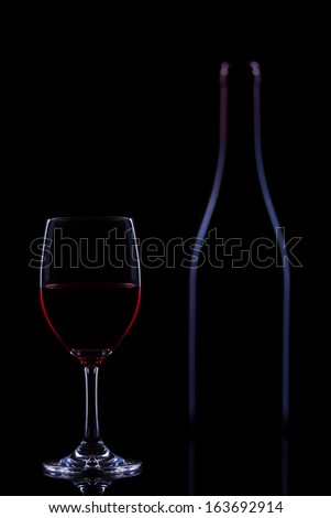 Red wine bottle and glass silhouette with black background