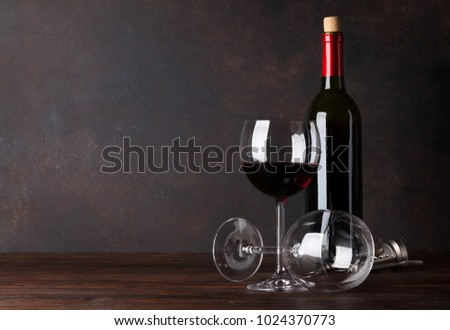 Red wine bottle and glasses in front of blackboard wall. With copy space for your text