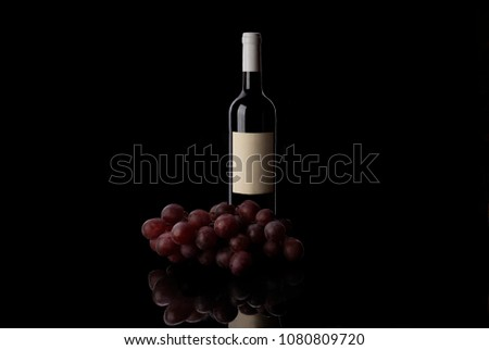 Red wine bottle and grape on black back ground