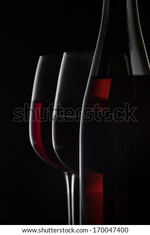 Red wine bottle and two wine glasses on black background