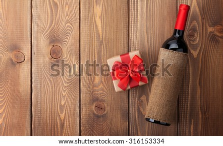 Red wine bottle and valentines day gift box. Over rustic wooden table background with copy space - stock photo