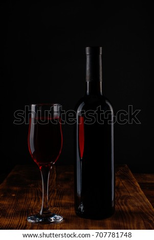 Red wine bottle and wine glass on a wooden background