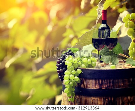 Red wine bottle and wine glass on old barrel. - stock photo