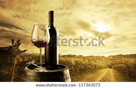 red wine bottle and wine glass on wodden barrel