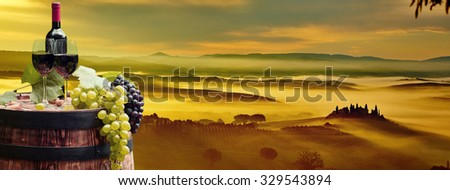 Red wine bottle and wine glass on wodden barrel. Beautiful Tuscany background - stock photo
