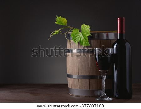 red wine bottle and wine glass on wooden barrel and the vine - stock photo