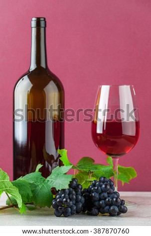 Red wine bottle and wineglass with ripe grapes on marble and pink background