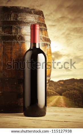 red wine bottle and wodden barrel, vineyard on background - stock photo