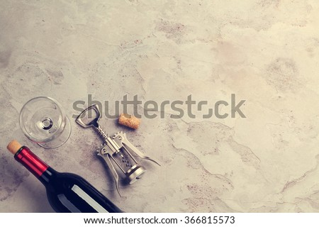 Red wine bottle, glass and corkscrew on stone table. Top view with copy space. Toned