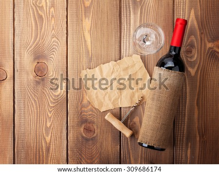 Red wine bottle, glass and corkscrew on wooden table background. Top view with copy space - stock photo