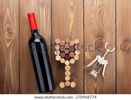 Red wine bottle, glass shaped corks and corkscrew. View from above over rustic wooden table background - stock photo