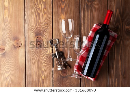 Red wine bottle, glasses and corkscrew on wooden table background. Top view with copy space - stock photo