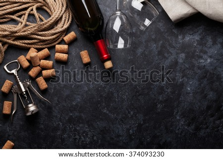 Red wine bottle, glasses and corkscrew over dark stone background. Top view with copy space - stock photo