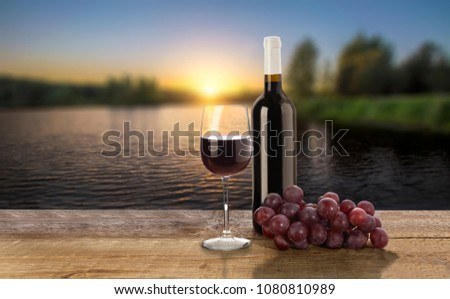 Red wine bottle, grape and wine glass on sunset background