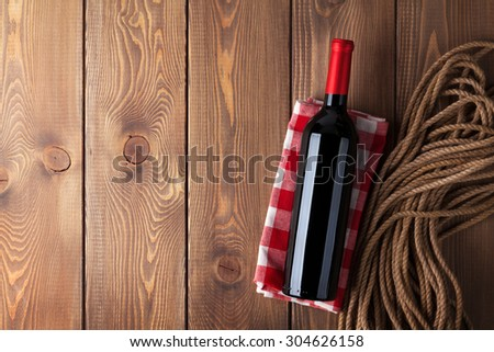Red wine bottle over rustic wooden table background with copy space - stock photo