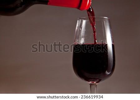 Red wine bottle pouring in wineglass. Isolated on dark background