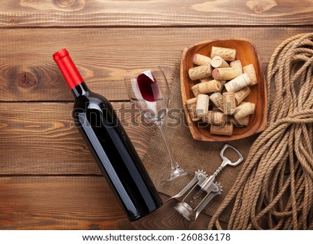 Red wine bottle, wine glass, bowl with corks and corkscrew. View from above over rustic wooden table background  - stock photo