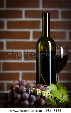 Red wine bottle with glass and grape on brick wall background - stock photo