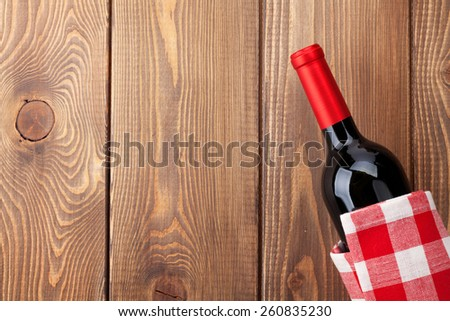 Red wine bottle with towel on wooden table background. Top view with copy space  - stock photo
