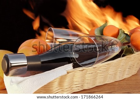 Red wine Bottle with two glasses lies in the basket on the background of fire. On the neck of the bottle is set to wine stopper - stock photo